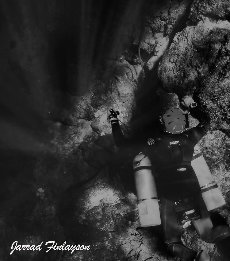 Scuba diver in side mount with rock formations underneath and sun light beams shining to the left in black and white.