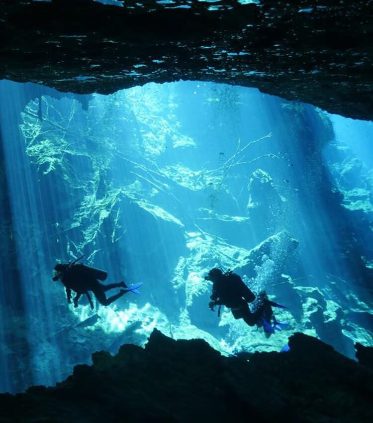 Two scuba divers in mid water, with rock formations and sun light beams in the background.