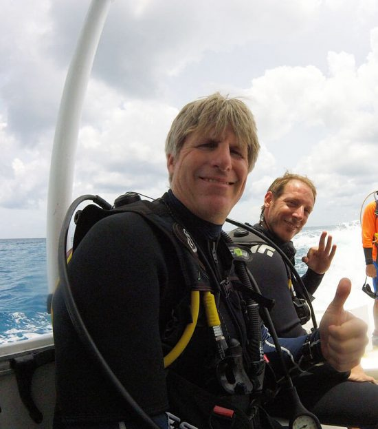 Two divers sitting side by side on a boat, fully set up in scuba gear signalling ok.