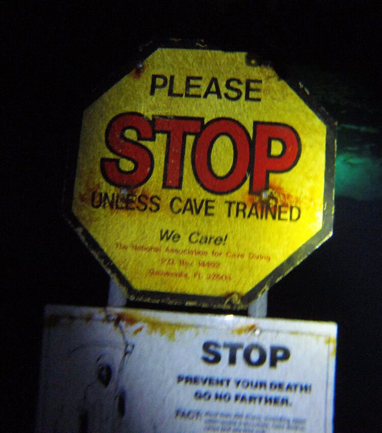 Octagonally sign that reads - PLEASE STOP UNLESS CAVE TRAINED in yellow, black and red, with smaller unreadable writing with a rectangular sign that is partly visible underneath in black and white with a grim reaper and the words - STOP and smaller unreadable writing.