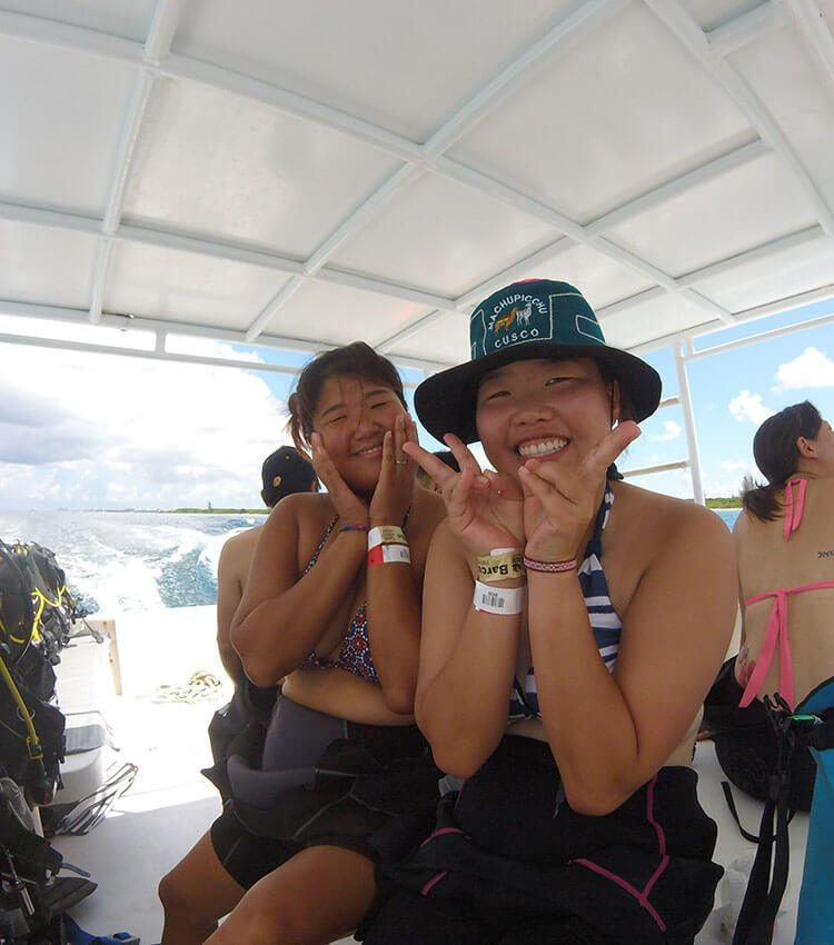 Two female divers wearing wetsuits sitting in the middle of the boat smiling for the photo.