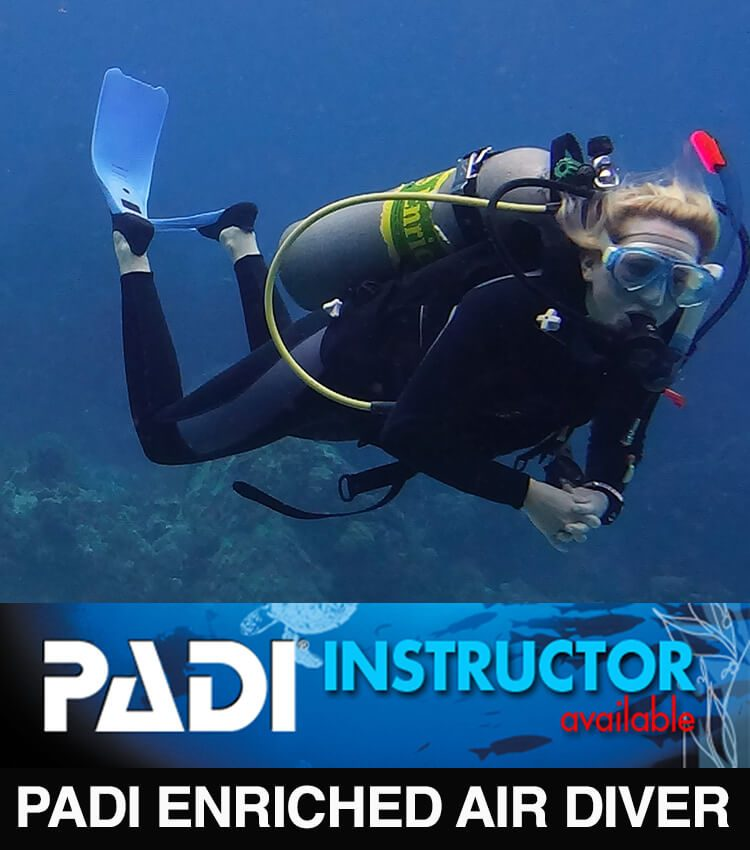Scubadiver in mid water with coral formations underneath and blue water in the background.