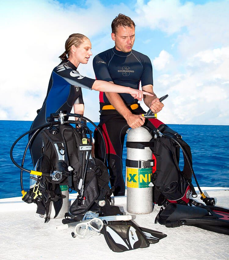Two scuba divers standing behind scuba tanks with scuba equipment connected, one is looking at the pressure gauge as one is pointing to it, they are standing on a pier with sea water behind them.