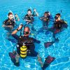 Five scuba divers in a circle standing in a swimming pool with their inflator hoses held up.